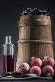 老酒瓶用葡萄、桶和葱 库存图片