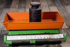 老重量和重量在一张木桌上 老使用的厨房标度 图库摄影