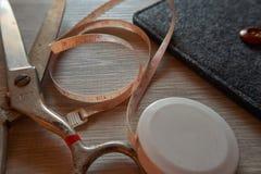 老金属剪刀和裁缝措施磁带在灰色木backgr 图库摄影