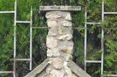 老金属篱芭和石头塔 库存照片