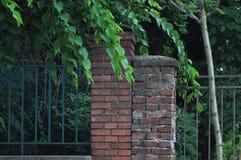 老金属篱芭和石头塔 免版税库存图片