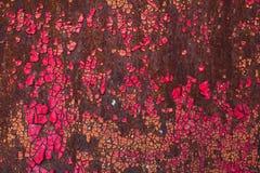 老金属表面上的破裂的红色油漆 库存照片