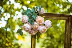 老金黄框架,装饰用花,垂悬在分支绿色背景 婚姻的照片写真的花卉装饰 库存图片