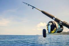 老钓鱼竿和蓝色海水 库存图片