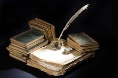 老钢笔、书和墨水池和银币在黑背景 免版税图库摄影