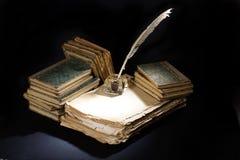 老钢笔、书和墨水池在黑背景 免版税库存照片