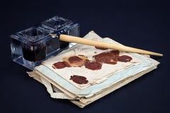 老钢笔和墨水池有老信件的在黑背景 库存照片