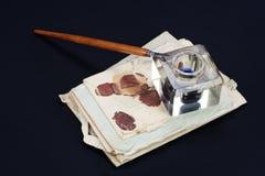 老钢笔和墨水池有老信件的在黑背景 图库摄影
