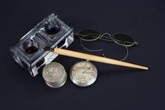 老钢笔和墨水池有银币的和怀表在黑背景 免版税库存照片