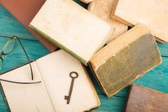 老钥匙、玻璃和堆在蓝色木书桌上的古色古香的书 库存图片
