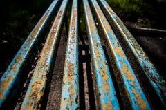 老铁生锈的长凳在公园 库存图片