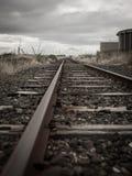 老铁路轨道在虚张声势,新西兰村庄  免版税库存照片