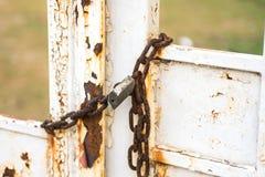 老铁锁在被关闭的一个生锈的门垂悬 免版税库存照片