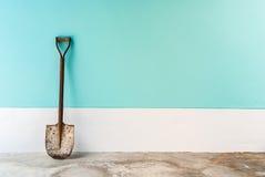 老铁锹用薄菏,深蓝淡色水泥墙壁 免版税库存照片