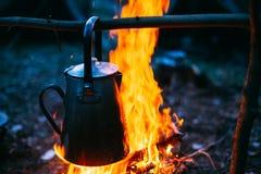 老铁阵营水壶煮沸在火的水在森林明亮的火焰火 免版税库存照片
