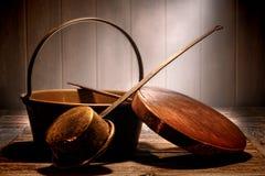 老铜罐和平底锅在变老的古色古香的厨房里 免版税库存照片