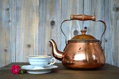 老铜茶壶和瓷茶杯 库存图片