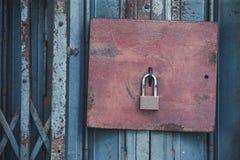 老锁和生锈的挂锁在一个老钢门与葡萄酒猪圈 库存照片