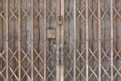 老锁着的可折叠的生锈的钢门 图库摄影