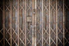 老锁着的可折叠的生锈的钢门 免版税图库摄影