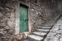 老锁着的绿色门和石头楼梯 库存图片