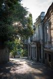 老镇初夏早晨的空的街道,太阳通过树枝发光 免版税库存照片
