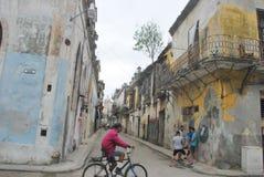 老镇看下来有人骑马周期的小巷的哈瓦那在前景 免版税库存图片