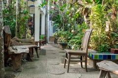 老长木凳和椅子在庭院里 免版税图库摄影
