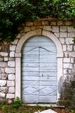 老门和窗口在一个石墙上 库存照片
