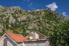 老防御墙壁曲折前行在科托尔,黑山后的小山 免版税库存图片