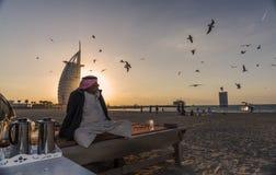 老阿拉伯人坐海滩 免版税库存照片