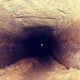 老隧道,被弄湿的墙壁 在砂岩岩石雕刻的干燥渠道 库存照片