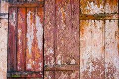 老难看的东西和被风化的红色,黄色和白色木墙壁板条构造背景 库存图片