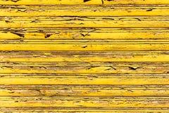 老难看的东西和被风化的黄色木墙壁板条构造对元素的长的暴露指示的背景 免版税图库摄影