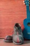 老鞋子和尤克里里琴 库存图片