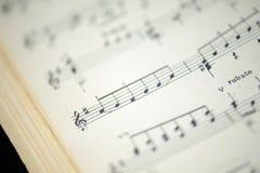 老音乐笔记本的页在黑暗的背景的 库存图片