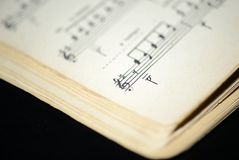老音乐笔记本的页在黑暗的背景的 库存照片