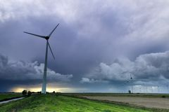 老风车和现代涡轮在风暴 免版税库存照片