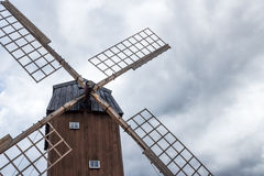老风车在多云天空下 免版税图库摄影