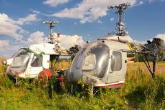 老飞机机体和生锈的直升机在绿草 免版税库存照片