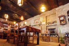 老餐馆砖墙有酒瓶的在架子、木桌和明亮的灯 免版税库存照片