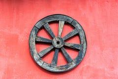 老马车车轮和红色墙壁 库存照片