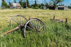 老马车车轮有老农舍、绕环投球法和容器的一个被放弃的大草原围场在背景中 免版税库存图片