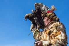 老鹰猎人传统衣物,当寻找对拿着在他的胳膊时的野兔一只鹫 免版税库存图片