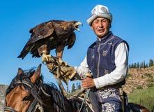 老鹰猎人在马背上拿着他的老鹰,准备采取飞行 免版税库存图片