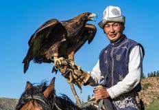 老鹰猎人在马背上拿着他的老鹰,准备采取飞行 免版税库存照片