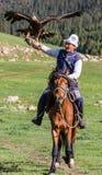 老鹰猎人在马背上拿着他的老鹰 图库摄影