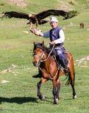老鹰猎人在马背上拿着他的老鹰 免版税库存图片