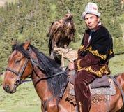 老鹰猎人在马背上拿着他的老鹰 免版税库存照片