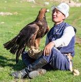 老鹰猎人拿着他的老鹰,坐地面 免版税库存图片
